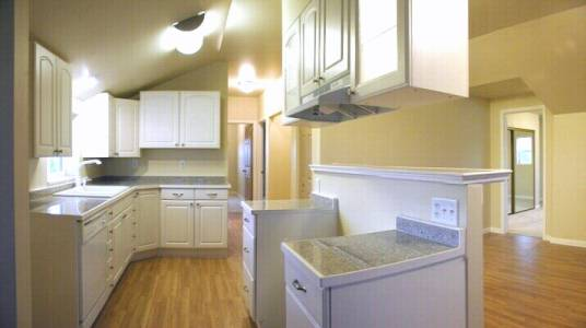 The new kitchen featured white cabinets and appliances and granite countertops